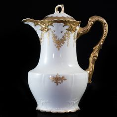 """Lot #26: Limoges Porcelain Pitcher DESCRIPTION: Limoges porcelain pitcher features in an off white ground color decorated with ornate gilded designs along the body and neck. Marked on the bottom """"Limoges France""""  CIRCA: Early to Mid 20th Ct. ORIGIN: France DIMENSIONS: H: 9.5″ L: 8″"""