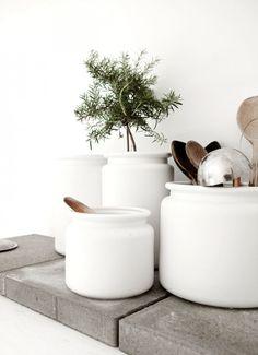 Landelijke sfeer door witte potten met keukengerei voor op het aanrecht