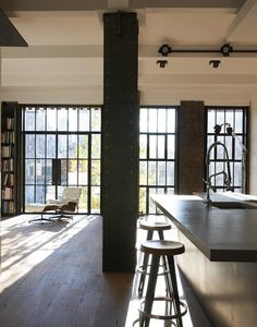 Industrial character and a simple material palette – white ceiling and sheetrock walls, black steel, reclaimed oak floors, and exposed masonry.
