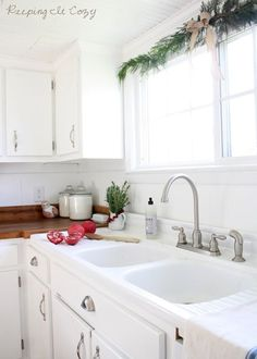 A little garland over the window and a little pot of rosemary next to the sink. Simple. (apartment therapy.com)