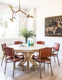 round table + leather and brass chairs (vintage Jacques Adnet leather chairs, a modern Roll & Hill Agnes chandelier and an Ilya Zomb oil-on-linen painting via C Home)