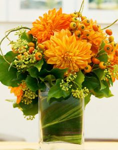 dahlia and ivy centerpiece with leaf wrapping the stems in the vase