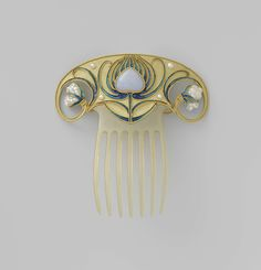Fan shaped gold hair comb, each side curling in a spiral to end in a baroque pearl; sytlized enameled flour in the center. Possibly German, circa 1900-1910