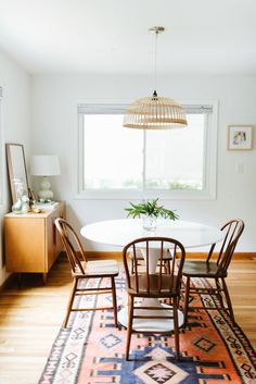 Cozy dining nook with a rattan pendant light, a bright area rug, and a marble table