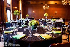 Black lattice linen overlays on round guest tables with lime green alternating low and candelabra floral arrangements | Hagerty  Photography | villasiena.cc