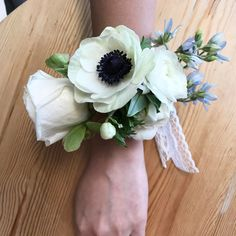Wedding wrist corsage for one of the mothers, made with rose, hellebore, anemone, ranunculus, and tweedia