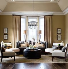 An oversized leather ottoman with nailhead trim acts as a coffee table in this cozy living room. Design by http://janelockhart.com/