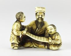 Netsuke of carved ivory, Jurojin seated with two boys in front holding a scroll: Japan, by Norishige, mid 19th century