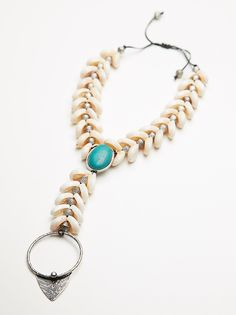 Siren Turquoise Shell Necklace   Beachy necklace adorned with cowrie shells, a statement turquoise stone and large metal pendant.    * Textured metal accents   * Adjustable chain