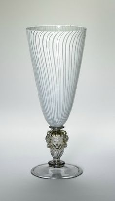 Goblet, glass, Venice, 1550-1600 Long oviform bowl resting on short, thick baluster stem and folded bell foot; bowl decorated with vertical white stripes, curving slightly at top and base. Height: 22.8 centimetres. Bequeathed by Felix Slade. S.591. British Museum. © Trustees of the British Museum.