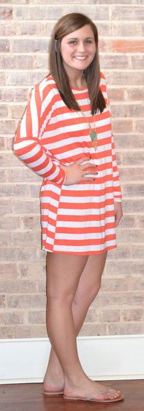 Orange and white striped tunic with simple sandals and a green necklace