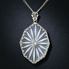 Art Deco camphor glass pendant necklace. Tiny diamond in the middle, silver filigree around the outside.