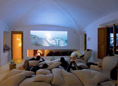 Home theater made for comfort! pillow bed on floor and beautiful long fireplace under the projector area