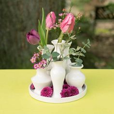Our grouping of ceramic bud vases is glazed in place on a circular tray, creating notable stability for your modern table centerpieces. Embellish the stylish round plate with vase filler, plant buds or flower petals for a lovely ornamental detail!