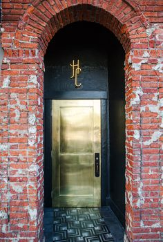 Exposed brick building with black and gold doorway.