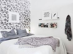 Cozy gray and white bedroom with floral wallpapered accent wall and floating shelves.