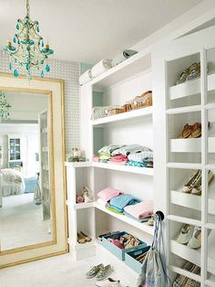neatly organized closet with white shelving and turquoise chandelier