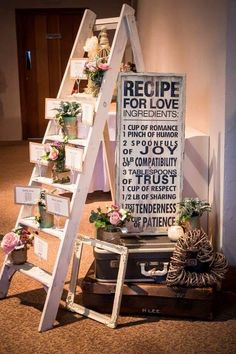 Step ladder with flowers in upcycled cans and table plan cards. Vintage props next to it to complete decoration.
