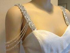 Custom made 1 inch wide rhinestone strap, on off-white satin. 3 lines of crystals drape off the strap onto the upper arm. The crystals drape can be positioned where you want.