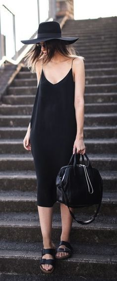 Black below-the-knee easy slip dress with a wide brim summer hat. Flat black Birkie sandals and big black bag. Sunnies. Elegant waif wandering the back streets. Style Planet