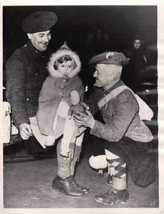 1941- Scottish soldiers try to cheer up a little girl who is waiting for a train to evacuate her from London.