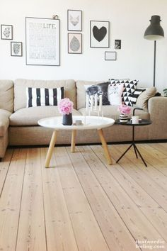 Wood floors + beige couch + black frame wall art + black floor lamp + white and wood coffee table