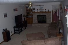 Furniture arrangement for small family room with a fireplace, and a TV on entertainment table.