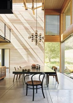 Thick rammed-earth walls, built by Stocker and Benchmark Development, curve along with the landscape and act as a central spine for the house. A hallway is marked by concrete floors.
