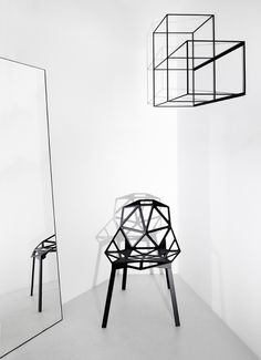 black acrylic cut out chair in a white space. modern.