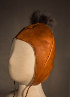 hand dyed vegetable tanned medieval style leather infant skullcap. Rabbit fur puff detail