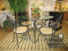 "Glass top table a dark metal base with four chairs. Love all the curves in this metalwork! The chairs have a tan and rust patterned seat. Excellent set for a more casual kitchen/dining area. 48""round."