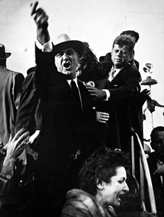 Lyndon B. Johnson yelling at the pilots of a nearby plane to cut their engines so that John F. Kennedy could speak as Kennedy is seen trying to calm him down. Photograph by Richard Pipes during the 1960 presidential campaign in Amarillo, Texas.