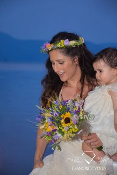 Gorgeous Bride with her child with a perfect bouquet of field flowers for her Boho Wedding beside the lake. Wildflowers and grasses make up a unique bouquet and a wreath! Check more at: https://www.instagram.com/diamond_event_planners/  https://plus.google.com/u/0/+DiamondeventsGr  https://gr.pinterest.com/diamondwedding/  https://www.facebook.com/Diamond-Event-Planners-176242063682/  http://diamondevents.gr/ #happy #illumination #india #inspiration  #israel #jars #kifisia #kuwait #lace…