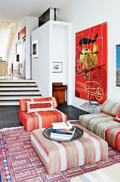 Living room with bright red art and red sofas.
