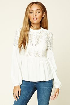 A floral lace top featuring a slightly flared crepe woven hem and button-cuff long sleeves, embroidered ornate stripes down the front, a buttoned keyhole cutout back, and a round neckline.