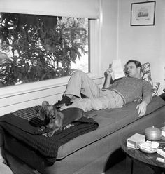 A chilled-out Marlon Brando reads lines for his role in The Men, during some downtime alongside his guard dachshund in LA in 1949.