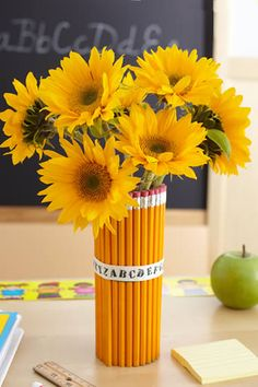 How to make a pencil vase - Clean out a peanut butter container, hot glue pencils (using the table as a leveling guide), then put a rubber band around the pencils. Cover the rubber band with cute ribbon then tie a bow. Use Colored Pencils.