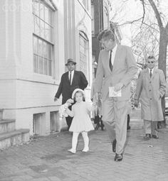 John F Kennedy Walking with Daughter Caroline Original caption: Clinging to her doll with one hand and her father's finger with the other, Caroline Kennedy walks with the President-elect from home to church on her third birthday today. Following the services, Kennedy took his daughter back home, then visited his wife and newborn son in Georgetown Hospital. The book in Kennedy's hand is a child's prayer book.  Date Photographed:November 27, 1960's