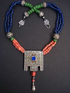 By Luda Hunter ~ Necklace 'Tiznit'. An old Moroccan enameled pendant from Tiznit with blue glass insert and 2 drops of antique Mauritanian coral and a silver hamsa for protection. 3 strands of antique Mauritanian coral and Indonesian blue and green glass beads, six Berber enamel beads, sterling silver beads and clasp.