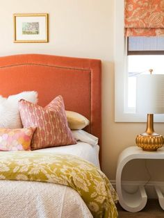 Orange velvet headboard, matte gold lamp, and nice combo of fabrics on the throw pillows and linens.