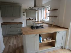 Nice colour cabinets- wood worktop with wooden flooring works.