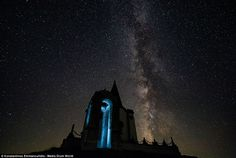 An ancient ruined church glows an eerie shade of blue, lit up against the backdrop of the ...