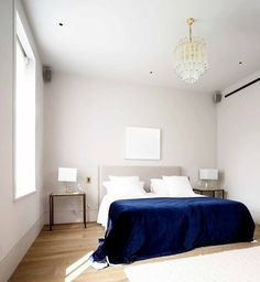 Simple white bedroom with chandelier, navy bedding, and two nightstands