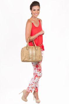 Qué tal este conjunto de blusa naranja combinado con un pantalón blanco estampado, accesorios dorados y un bolso en color nude a juego con los zapatos.
