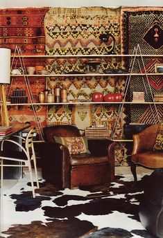 An eccentric handmade shelf, with a backdrop of an assortment of kilim wall tapestries, a cowhid rug on the floor, a more industrial office chair and desk to the left (from what I can make out)... all give this space its liveliness, pattern, texture and undeniable bohemian chic.