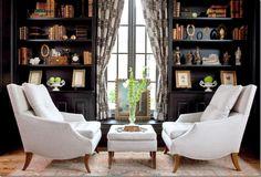 Love the white chairs against dark walls and soooooo many books!