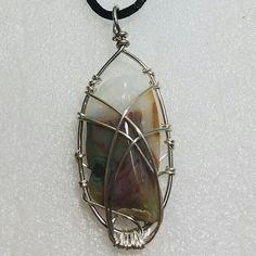 Silver caged multicolor Madagascar Ocean Jasper pendant on black rope necklace.