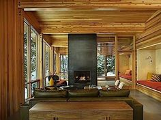 12 Fabulous Fireplaces: In what seems to be a modern rustic, wood-clad sunroom, Seattle-based firm DeForest Architects used a contrasting black finish on the floor-to-ceiling fireplace that stands smack in the middle of the space.