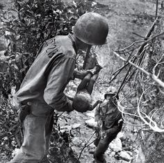 U.S. Marine with the child in his arms in the jungles of Saipan
