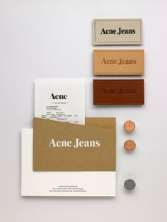 Design: Acne Art Department  A small selection of branding material. Clockwise from top right are jeans labels, denim buttons, a compliments slips and a receipt envelope.